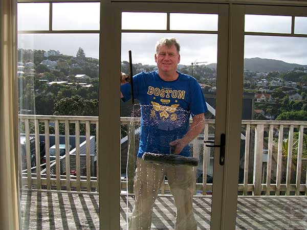 John the Window Cleaner washing a glass door